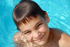 Teen boy in swimming pool portrait. Happy teen boy in blue swimming pool portrait Stock Photos