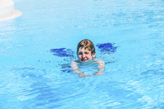Teen boy swimming in a pool. Smiling teen boy swimming in a pool Royalty Free Stock Photo