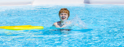 Teen boy swimming in a pool. Smiling teen boy swimming in a pool Royalty Free Stock Images