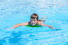 Teen boy swimming in a pool. Smiling teen boy swimming in a pool Stock Photo