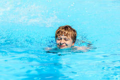 Teen boy swimming in a pool. Smiling teen boy swimming in a pool Royalty Free Stock Photography