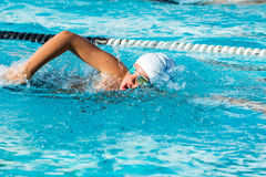 Teen boy at swimming practice. Close up action shot of Teen boy swimming freestyle at swimming lesson royalty free stock photo