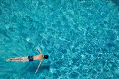 Teen boy swimming underwater in a pool outdoors royalty free stock image