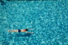 Teen boy swimming underwater in a pool outdoors royalty free stock photo