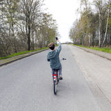 Teen boy takes a selfie while cycling on the road Stock Image