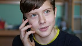 Teen boy talking on the phone indoor smartphone Royalty Free Stock Photos