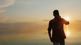 Teen boy talking on the phone. Near the sea at sunset stock video