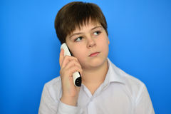 Teen boy talking by radiotelephony on a blue background Royalty Free Stock Photo