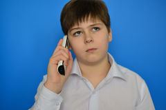 Teen boy talking by radiotelephony on a blue background Royalty Free Stock Image