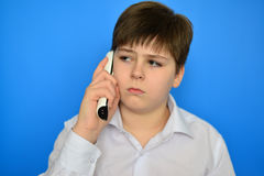 Teen boy talking by radiotelephony on a blue background Stock Photo
