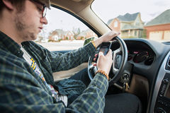 Teen boy texting and driving dangerous distracted. Teen boy driving a car while texting on a smart phone distracted driver dangerous Stock Photos
