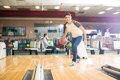 Teen Boy Throwing Ball While Practicing Bowling Game In Club Royalty Free Stock Images