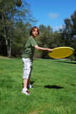 Teen Boy Throwing Frisbee. Teen boy throwing yellow frisbee with green grass, trees, and blue sky in the background Royalty Free Stock Photo