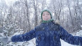 Teen boy throws snow in the winter forest. Active lifestyle, winter activity, outdoor winter games concept. Happy Teen boy throws snow in the winter forest stock footage