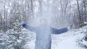 Teen boy throws snow in the winter forest. Active lifestyle, winter activity, outdoor winter games concept. Happy Teen boy throws snow in the winter forest stock video