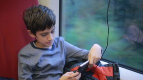 Teen boy traveling on the train. Teen boy travel in a train and playing on your phone stock video