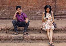Teen boy Upset with Indifferent Girl Friend. Teen girl and boy sitting in brick steps. Boy unhappy with girl friend's obsession for mobile phone. Shows royalty free stock image