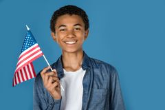 Teen boy with usa flag. Isolated on blue stock images