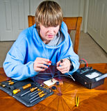 Teenager Using A Ohmmeter. Teen boy uses an ohmmeter to measure resistance across a circuit for a science project royalty free stock images
