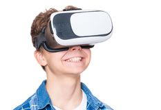 Teen boy in VR glasses. Happy teen boy wearing virtual reality goggles watching movies or playing video games, isolated on white. Cheerful teenager looking in VR Stock Images