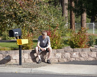 Teen boy waits by mailbox Stock Image