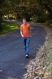 Teen boy walking. Handsome teen boy walking on curving road in fall Stock Image