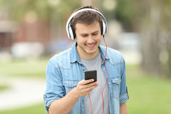 Teen boy walking and listening on line music. Front view of a teen boy walking towards camera and listening on line music outdoors in a park Royalty Free Stock Photography