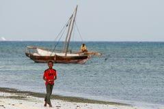 Teen boy walks on coast Indian Ocean, near fishing boat. Royalty Free Stock Photo