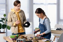 Teen boy watching how female teenager brazing computer circuit with soldering iron. At home stock images