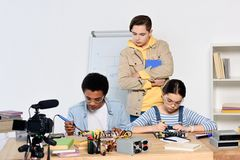 Teen boy watching how multicultural friends soldering computer circuit with soldering iron. At home stock photo