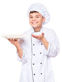 Teen boy wearing chef uniform. Cheerful handsome teen boy wearing chef uniform. Portrait of a happy cute male child cook with empty plate, isolated on white Stock Photos