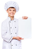 Teen boy wearing chef uniform. Cheerful handsome teen boy wearing chef uniform. Portrait of a happy cute male child cook with plastic chopping board for menu Stock Photos
