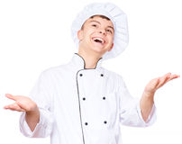 Teen boy wearing chef uniform. Cheerful handsome teen boy wearing chef uniform. Portrait of a happy cute male child cook with raising hands, isolated on white Royalty Free Stock Photography