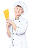 Teen boy wearing chef uniform. Cheerful handsome teen boy wearing chef uniform. Portrait of a happy cute male child cook with raw spaghetti, isolated on white Stock Photo