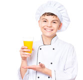 Teen boy wearing chef uniform. Handsome teen boy wearing chef uniform drinking fresh orange juice. Portrait of a happy cute male child cook with glass, isolated Stock Image