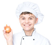 Teen boy wearing chef uniform. Handsome teen boy wearing chef uniform holding fresh onion. Portrait of a happy cute male child cook, isolated on white background Stock Images