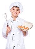 Teen boy wearing chef uniform. Handsome teen boy wearing chef uniform holding hand mixer or wire whisk. Portrait of a happy cute male child cook with eggs and Stock Photo