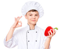 Teen boy wearing chef uniform. Handsome teen boy wearing chef uniform making ok gesture and holding red pepper. Portrait of a happy cute male child cook Stock Photo