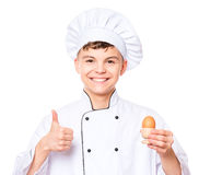Teen boy wearing chef uniform. Handsome teen boy wearing chef uniform making thumbs up gesture and holding brown egg. Portrait of a happy cute male child cook Stock Image