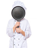 Teen boy wearing chef uniform. Handsome teen boy wearing chef uniform. Portrait of a happy cute male child cook hiding behind a frying pan for menu, isolated on Royalty Free Stock Photos