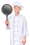 Teen boy wearing chef uniform. Handsome teen boy wearing chef uniform. Portrait of a happy cute male child cook hiding behind a frying pan for menu, isolated on Stock Image