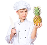 Teen boy wearing chef uniform. Handsome teen boy wearing chef uniform. Portrait of a happy cute male child cook with knife and pineapple,  on white background Stock Photography