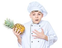 Teen boy wearing chef uniform. Handsome teen boy wearing chef uniform holding ananas. Portrait of cute male child cook with pineapple, isolated on white Royalty Free Stock Photo