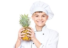 Teen boy wearing chef uniform. Handsome teen boy wearing chef uniform holding ananas. Portrait of a happy cute male child cook with pineapple, isolated on white Stock Photo