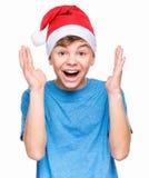 Teen boy wearing Santa Claus hat. Half-length emotional portrait of caucasian teen boy wearing Santa Claus hat, surprised. Teenager in blue t-shirt looking at Stock Photo