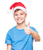 Teen boy wearing Santa Claus hat. Half-length portrait of caucasian teen boy wearing Santa Claus hat. Teenager looking at camera and making thumb up gesture Royalty Free Stock Photos