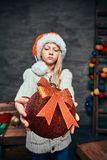 Teen boy wearing Santa`s hat holding a big Christmas ball in a dark room with a decorated wooden ladder. royalty free stock image