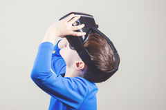 Teen boy wearing virtual reality glasses watching movies or playing video games Stock Photos