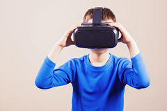 Teen boy wearing virtual reality glasses watching movies or playing video games Royalty Free Stock Images