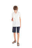 A teen boy with a mobile phone. A teen boy wearing a white shirt with a mobile phone Royalty Free Stock Image